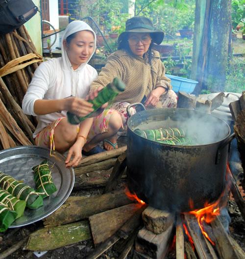 Le bánh tét est cuit au feu de bois de 4 à 5 heures. Ensuite, on le coupe en tranches.